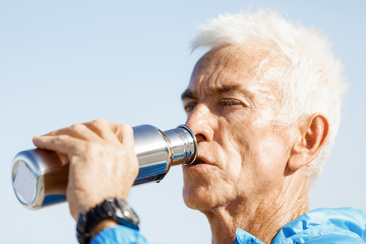 man drinking from stainless steel bottle